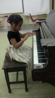 Janai getting comfortable with the piano at Suburban Music School